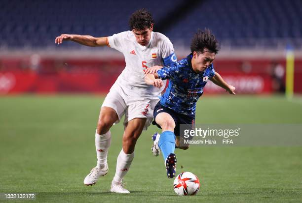 Reo Hatate of Team Japan is challenged by Jesus Vallejo of Team Spain during the Men's Football Semi-final match between Japan and Spain on day...