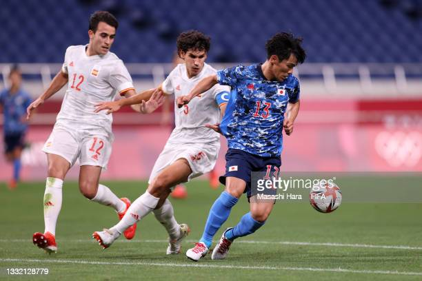 Reo Hatate of Team Japan is pulled back by Eric Garcia and Jesus Vallejo of Team Spain during the Men's Football Semi-final match between Japan and...