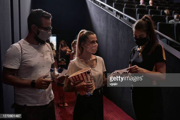 reopening cinema after coronavirus pandemic - couple talking with movie theater usher - audience stock pictures, royalty-free photos & images