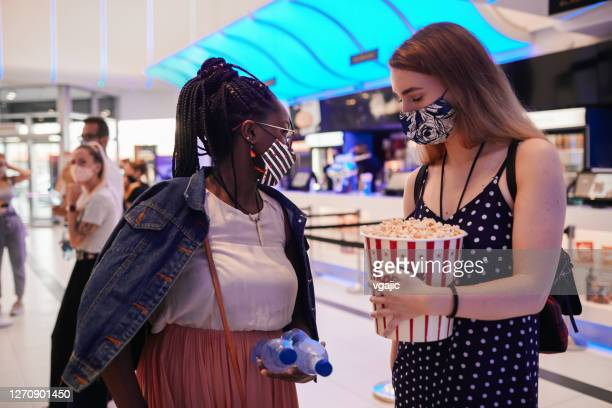 reopening cinema after coronavirus - two young woman standing in cinema lobby - between two ferns: the movie stock pictures, royalty-free photos & images