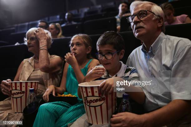 reopening cinema - happy family watching movie - reopening stock pictures, royalty-free photos & images
