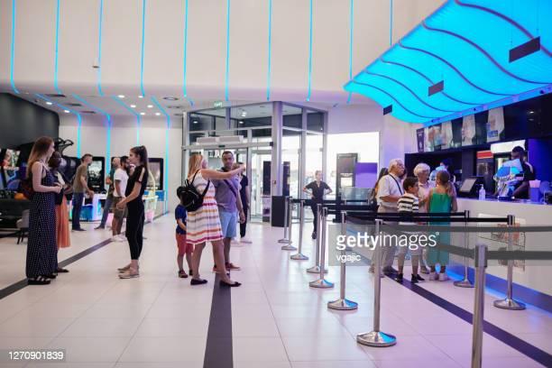 heropening cinema - mensen kopen filmkaartjes bij concession stand in cinema - filmpremière stockfoto's en -beelden
