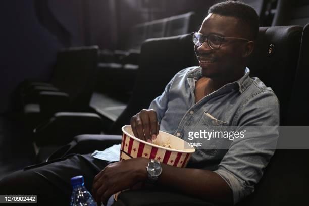 reapertura del cine - joven hombre africano disfrutar película - presentación de la película fotografías e imágenes de stock