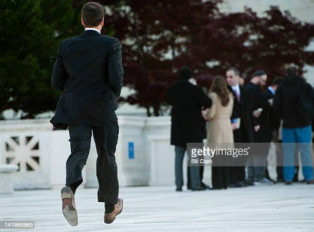 Rep Aaron Schock RIll runs across the plaza of the Supreme Court at 959AM to attend hear the court's arguments on the health care reform bill slated...