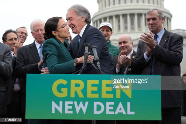 S Rep Alexandria OcasioCortez and Sen Ed Markey hug each other as other Congressional Democrats look on during a news conference in front of the US...