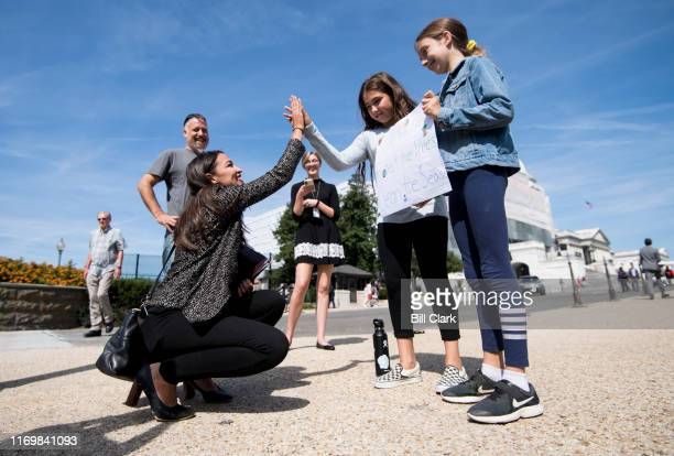 Rep Alexandria OcasioCortez DNY highfives climate striking students Evelyn Seek center and Pema Duncan right as they hold their climate strike sign...