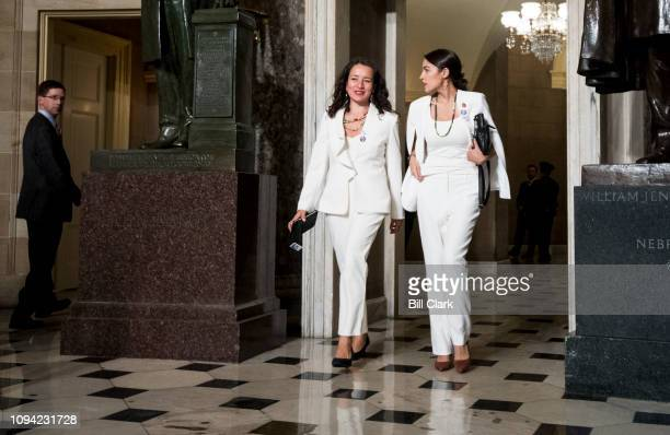 Rep Alexandria OcasioCortez DNY right walks with her State of the Union guest Ana Maria Archila to the House chamber for President Donald Trump's...