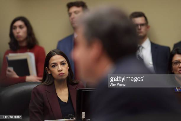 Rep Alexandria OcasioCortez listens to testimony by Michael Cohen former attorney and fixer for President Donald Trump before the House Oversight...