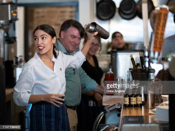 Rep. Alexandria Ocasio-Cortez shakes a margarita behind the bar at the Queensboro Restaurant, May 31, 2019 in the Queens borough of New York City....