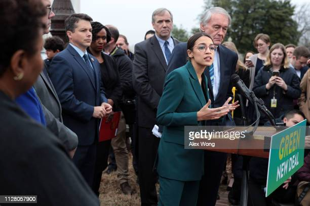 S Rep Alexandria OcasioCortez speaks as Sen Ed Markey listens during a news conference in front of the US Capitol February 7 2019 in Washington DC...