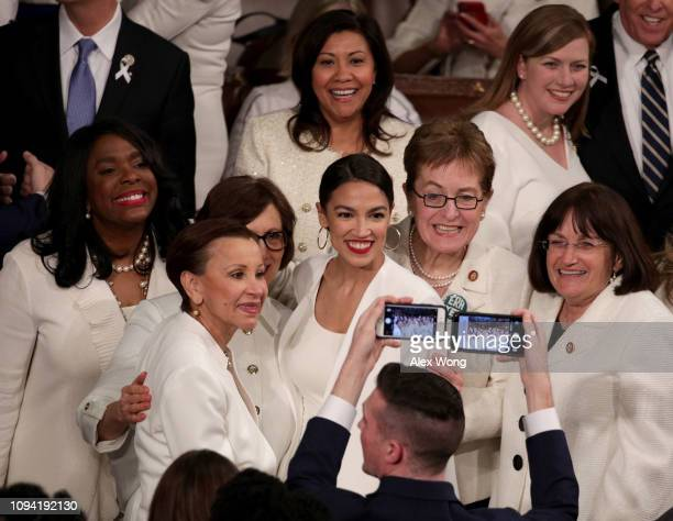 S Rep Alexandria OcasioCortez takes a group photo with fellow lawmakers ahead of the State of the Union address in the chamber of the US House of...