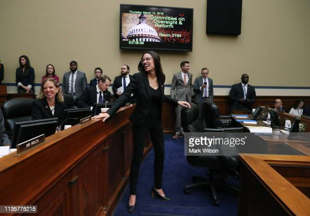 S Rep Alexandria OcasioCortez talks with fellow members during a House Oversight and Reform Committee hearing on March 14 2019 in Washington DC...