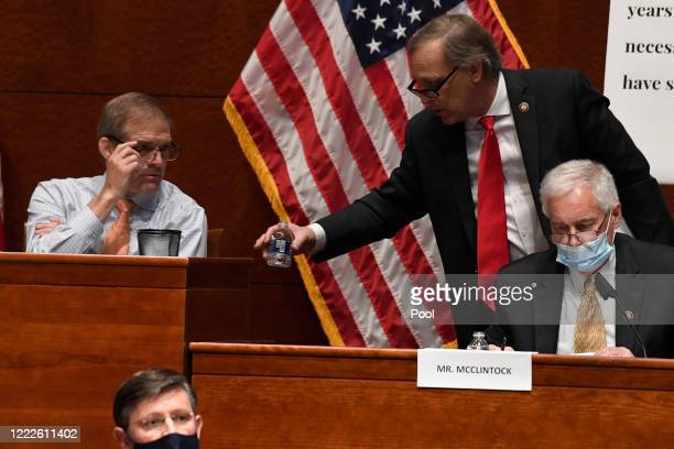 Rep Andy Biggs second from right talks with Rep Jim Jordan left during a House Judiciary Committee hearing on oversight of the Justice Department and...
