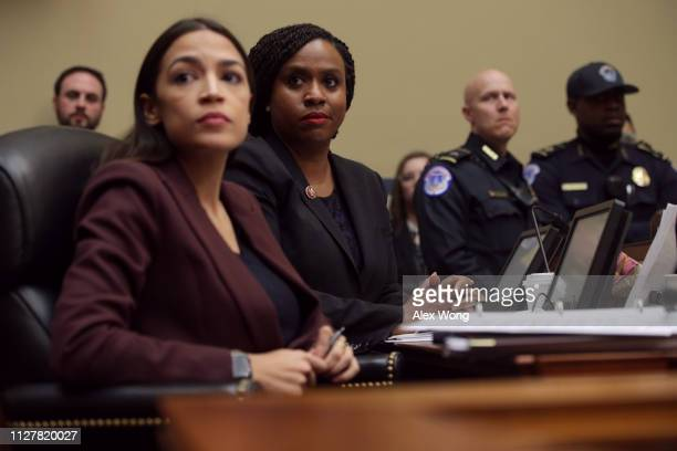 Rep Ayanna Pressley and Rep Alexandria OcasioCortez listen to Michael Cohen former attorney and fixer for President Donald Trump as he testifies...