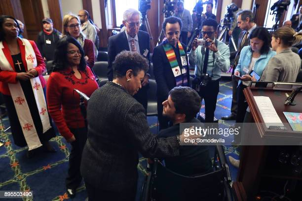 Rep Barbara Lee talks with Ady Barkan who lives with Amyotrophic Lateral Sclerosis following a rally against the GOP tax bill in the Rayburn Room at...