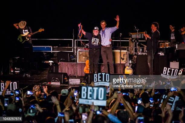 Rep Beto O'Rourke joined by singer Willie Nelson waves to supporters at a campaign rally at Auditorium Shores on September 29 2018 in Austin Texas...