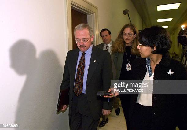 Rep Bob Barr enters a Republican Managers meeting late 13 January as a television light casts his shadow on the wall inside the House of...
