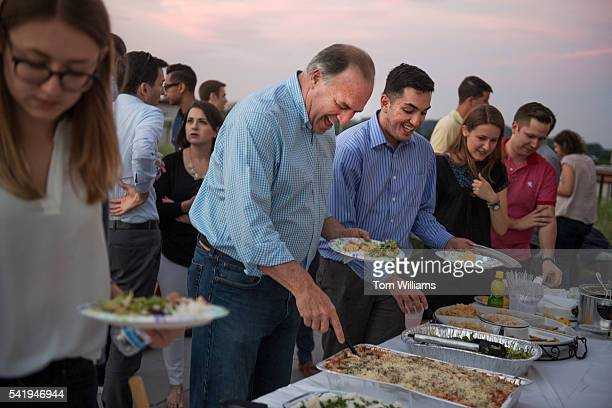 Rep Dan Kildee DMich serves himself during an iftar dinner on a roof deck in Northeast for guests who participated in fasting for Ramadan June 20...
