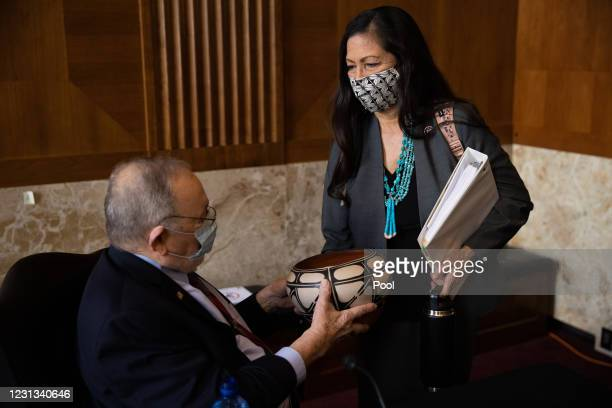 Rep. Deb Haaland , nominee for Secretary of the Interior, delivers a gift to Rep. Don Young at her confirmation hearing before the Senate Committee...