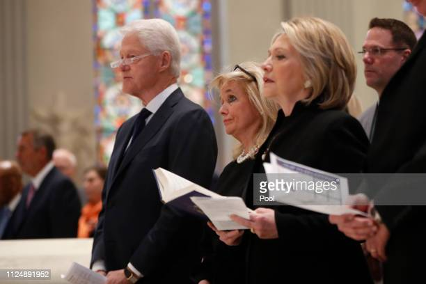 Rep. Debbie Dingell , center, stands with former President Bill Clinton and former Secretary of State Hillary Clinton during funeral services for her...