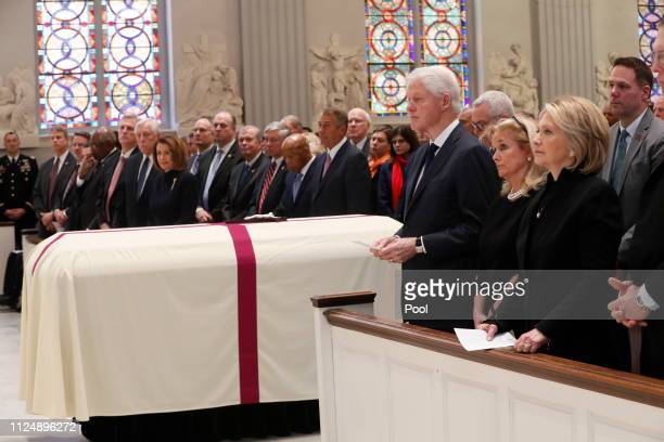Rep. Debbie Dingell , center, stands with former U.S. President Bill Clinton and former Sec. Of State Hillary Clinton, during funeral services for...