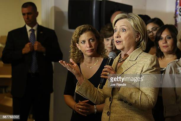 Rep Debbie Wasserman Schultz looks on as Democratic presidential nominee Hillary Clinton speaks as she stops by her campaign headquarters on August 9...