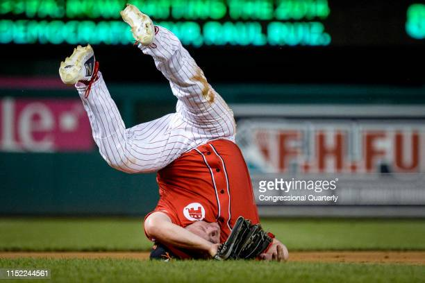 Rep Denver Riggleman RVa rolls over on his head as he catches the ball during the 58th annual Congressional Baseball Game at Nationals Park on...