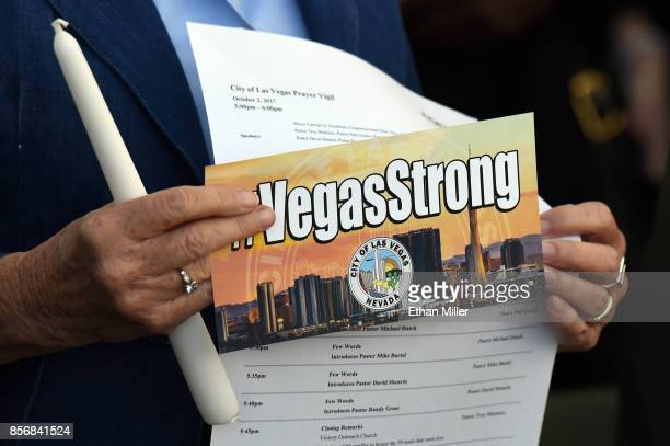 S Rep Dina Titus holds a candle and a #VegasStrong flyer during a prayer vigil outside Las Vegas City Hall in response to Sunday's mass shooting on...