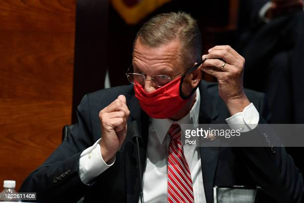 Rep Doug Collins puts on his mask during a House Judiciary Committee hearing on oversight of the Justice Department and a probe into the...