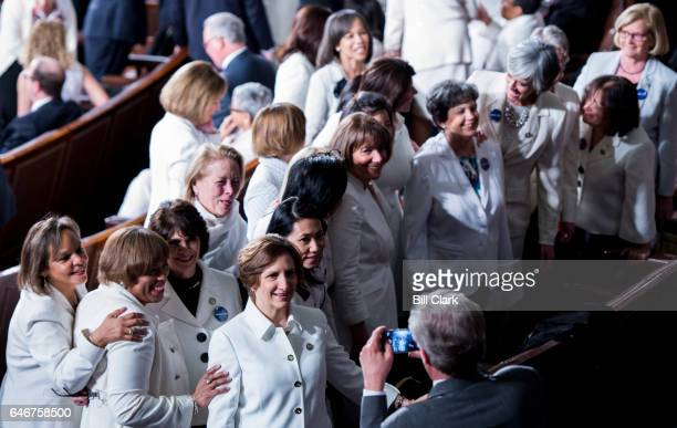 Rep Frank Pallone DNJ takes a group photo of women Democrats wearing all white for President Donald Trump's address to a joint session of Congress on...