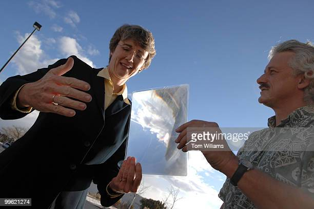 Rep Heather Wilson RNM is shown a lens sunlight concentrating lens for a solar steam generator by Charles Shults at San Juan College in Farmington NM