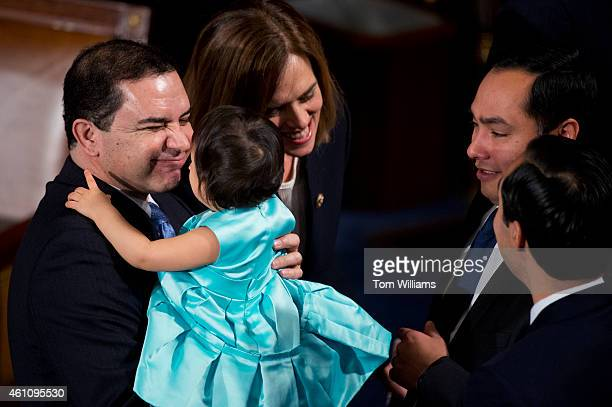 Rep Henry Cuellar DTexas holds Andrea Elena Castro daughter of Joaquin Castro DTexas second from right before the 114th Congress was sworn in on the...