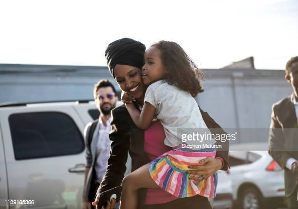 Rep. Ilhan Omar carries her daughter Ilwad as she arrives at a town hall meeting on gender pay gap and equity at La Doña Cerveceria on April 24, 2019...