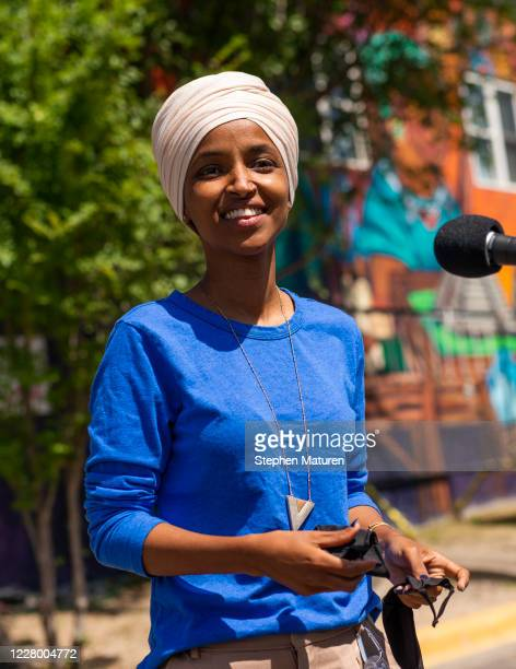 Rep Ilhan Omar removes her mask to speak with media gathered outside Mercado Central on August 11 2020 in Minneapolis Minnesota Omar is hoping to...