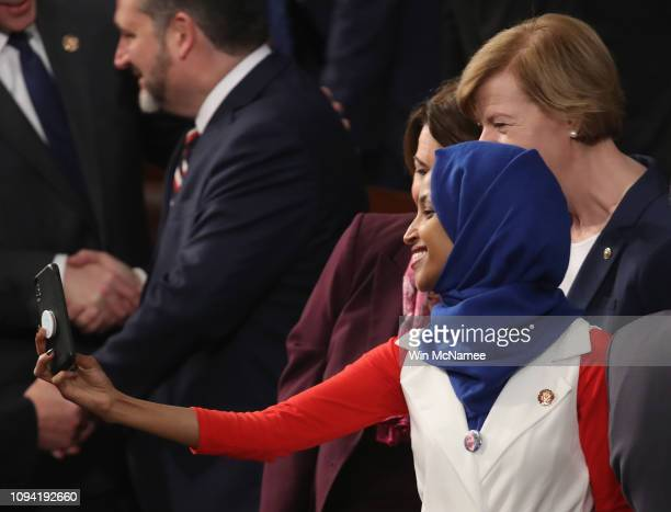 Rep Ilhan Omar takes a selfie with fellow lawmakers ahead of the State of the Union address in the chamber of the US House of Representatives at the...