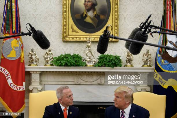 Rep Jeff Van Drew who is switching from the Democratic Party to the Republican Party sits with US President Donald Trump during a meeting in the Oval...