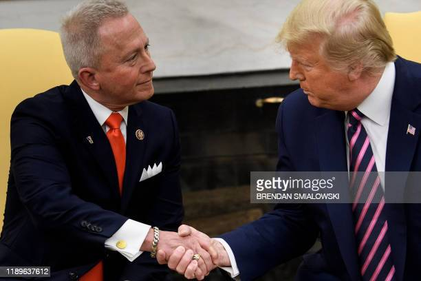 Rep Jeff Van Drew who is switching from the Democratic Party to the Republican Party shakes hands with US President Donald Trump during a meeting in...