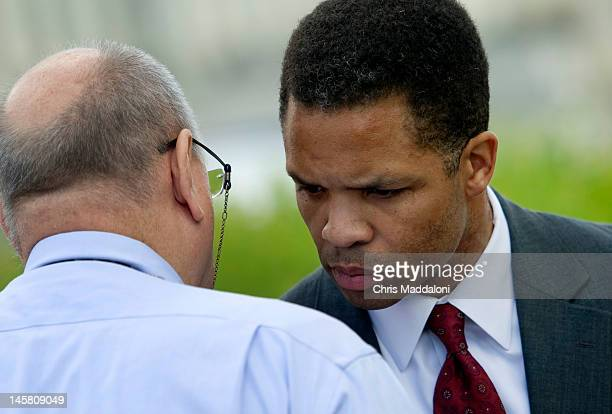 Rep Jesse Jackson Jr DIll speaks to his press secretary Frank Watkins at a news conference to discuss the introduction of legislation to raise the...