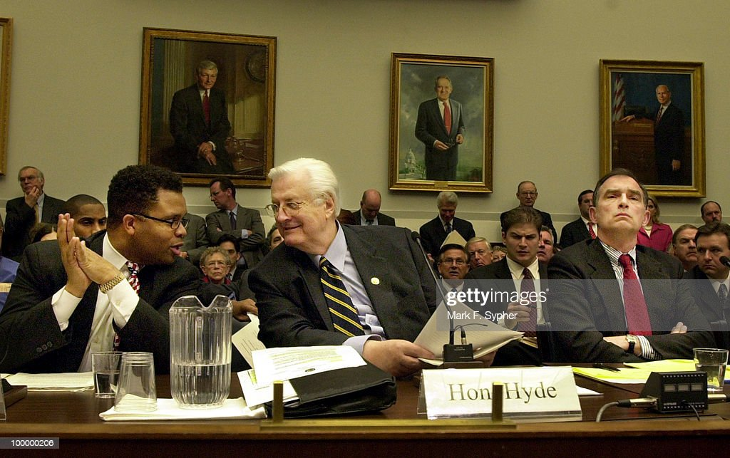 Rep. Jesse Jackson Jr. (D-IL), left, converses with Rep. Henry Hyde (R-IL), center, while Rep. Peter Visclosky (D-IN) listens to the chair's remarks, during an Aviation subcommittee hearing on H.R. 3479, the National Aviation Capacity Expansion Act.