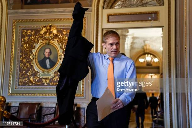 Rep Jim Jordan puts on a jacket before heading into the Senate cloakroom before the start of the Senate impeachment trial at the US Capitol on...