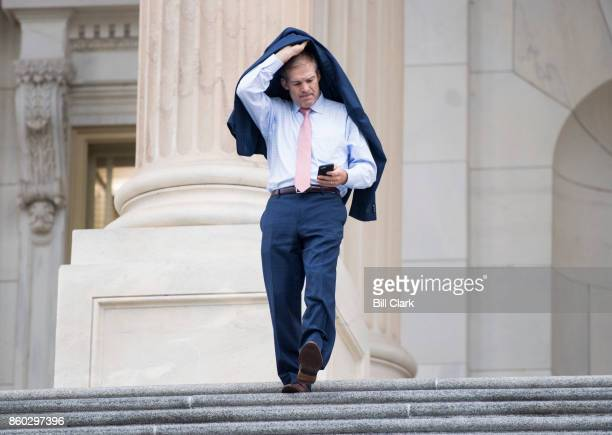 Rep Jim Jordan ROhio holds his jacket over his head as he walks down the House steps in a light rain following a vote on Wednesday Oct 11 2017