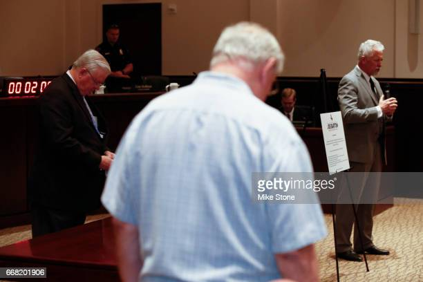 Rep Joe Barton left bows his head as his town hall meeting is opened in prayer at Mansfield City Hall on April 13 2017 in Mansfield Texas A capacity...