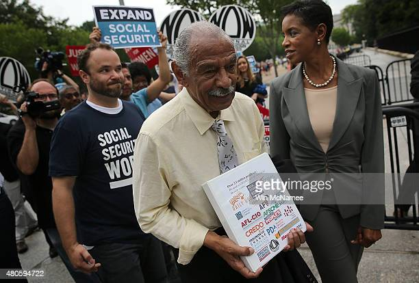 Rep John Conyers and Rep Donna Edwards carry petitions to the White House supporting the expansion of Social Security benefits following a rally July...