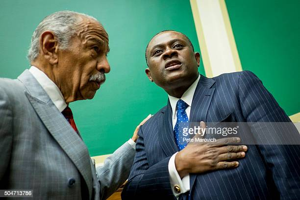 Rep John Conyers greets forensic pathologist and neuropathologist Dr Bennet Omalu before a briefing sponsored by Rep Jackie Speier on Capitol Hill on...