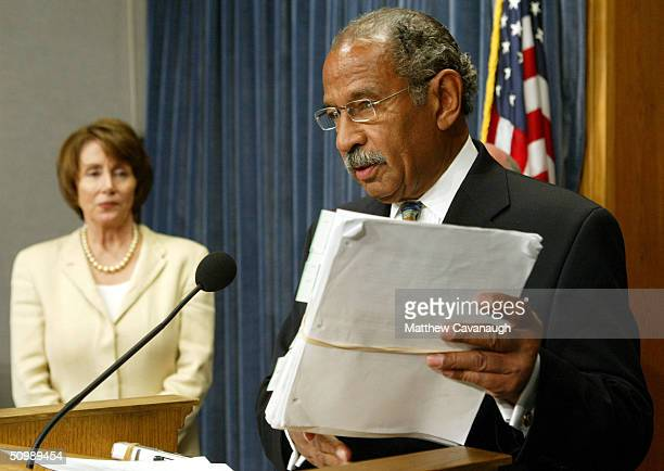 S Rep John Conyers holds a stack of recently released documents on the Abu Ghraib prison during a news conference with House Democratic Leader Nancy...