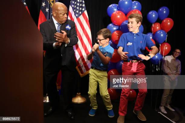 Rep John Lewis dances on stage before giving a speech in support of Democratic candidate Jon Ossoff at an election night party being held at the...