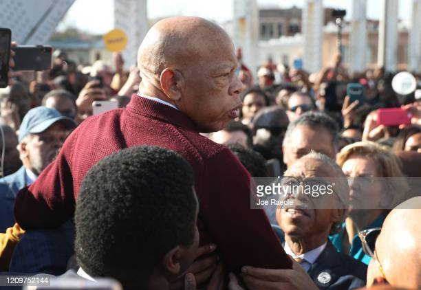 Rep. John Lewis is held aloft by Rev. Al Sharpton and others as he speaks to the crowd at the Edmund Pettus Bridge crossing reenactment marking the...