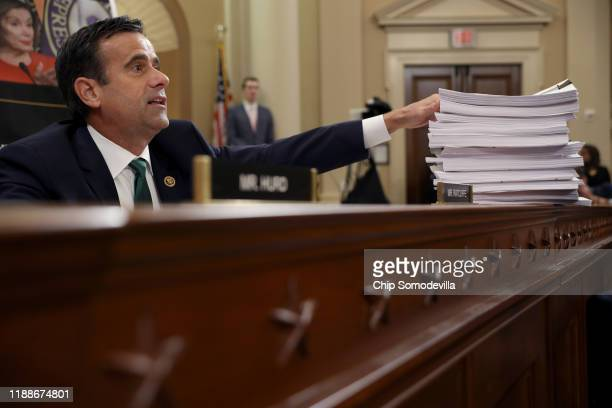 Rep John Ratcliffe gestures to a stack of transcripts of depositon as Lt Col Alexander Vindman National Security Council Director for European...