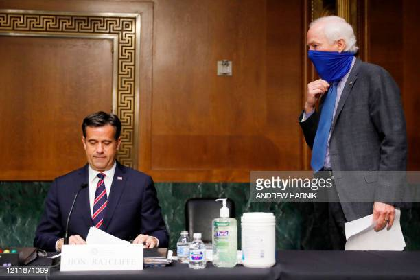 Rep. John Ratcliffe, R-TX, reviews his papers as Sen. John Cornyn, R-TX walks up, at the top of a Senate Intelligence Committee nomination hearing on...