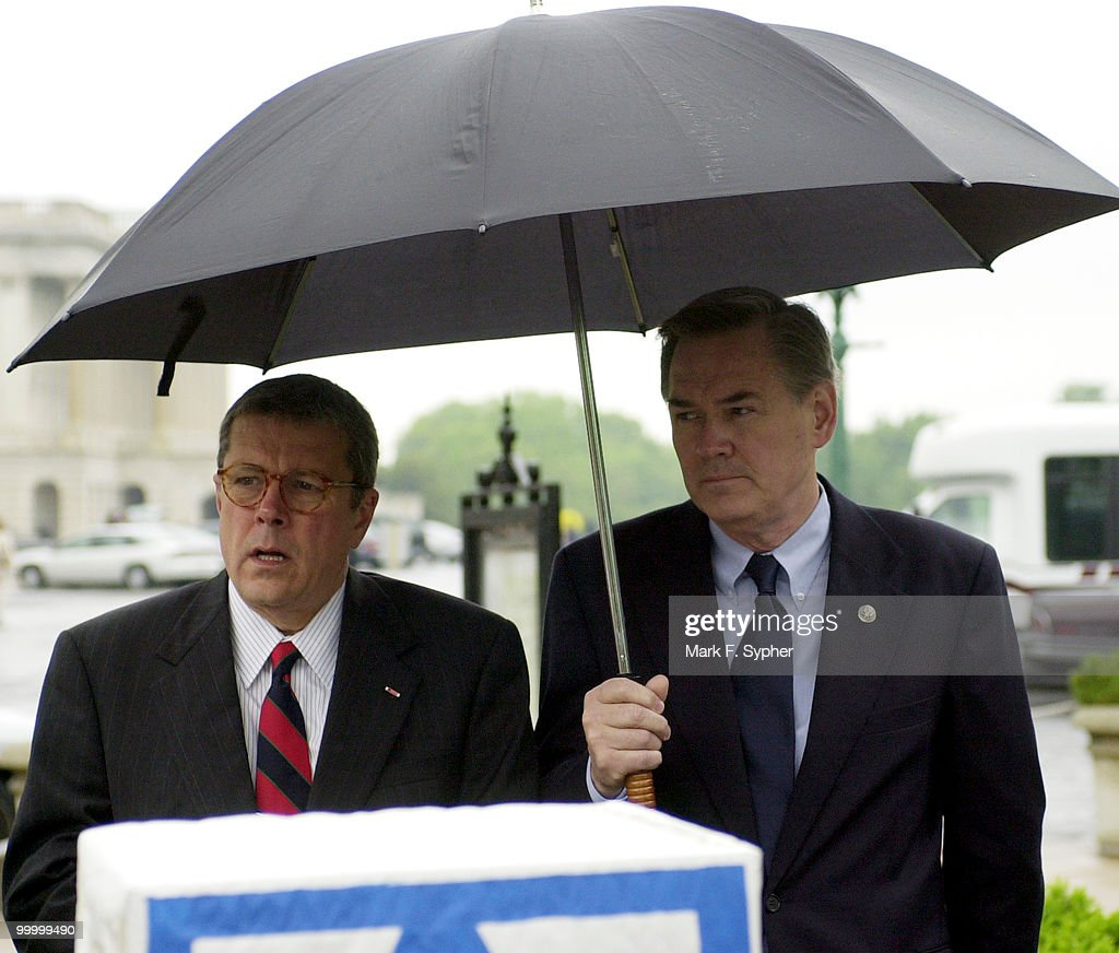 Rep. John S. Tanner (D-TN) and Rep. Dennis Moore (D-KS) find a common shelter during a rainy press conference on Thursday at the House Triangle which outlined 'The ABC's of Securing our Children's Future.'